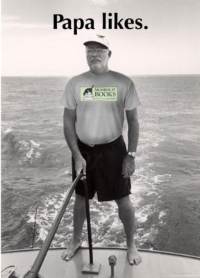 Papa Hemingway is standing on the deck of a sail boat out at sea. He appears to be steer the sail. And he's wearing a tee shirt with the Monroe Street Books logo on it.